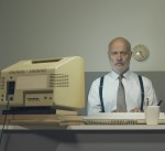 Man sits at desk with old computer.